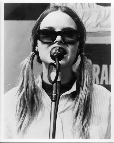 michelle_phillips_singing_at_a_microphone_wearing_sunglasses_and_hair_in_pigtails